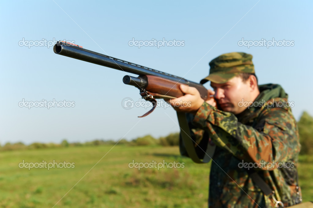 Male hunter in camouflage clothes on the field aiming the hunting rifle during a hunt. — Stock Photo #7142364