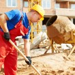 Builder worker at construction site with shovel — Stock Photo