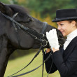 Horsewoman jockey in uniform with horse - Stock Photo