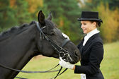 Horsewoman jockey in uniform with horse — Stock Photo