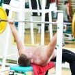 Bodybuilder lifting weight at sport gym — Stock Photo