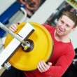 Bodybuilder loading weight at sport gym — Stock Photo