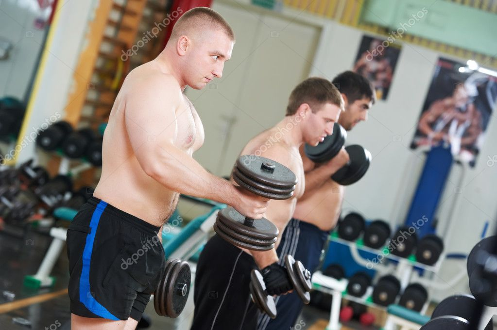 Young powerful muscular bodybuilders training with weight at sporting gym — Stock Photo #7401553