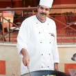 Stock Photo: Arab chef frying meat on pan
