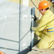 Facade Plasterer at exterior insulation work - Stock Photo