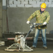 Worker trowelling and finishing of concrete - Stock Photo