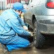 Machanic repairman at tyre fitting - Stock Photo