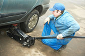 Machanic repairman at tyre fitting with car jack — Stock Photo
