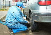 Machanic repairman at tyre fitting — Stock Photo