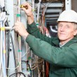 Mature electrician working in white hard hat with cables and wires — Stock Photo #7181632