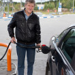 Mature man filling the modern car with gasoline in gas stations — Stock Photo