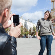 Man photographing young beautiful woman against city`s attractions. — Stock Photo