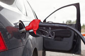 Refueling nozzle in the tank black car at fuel filling column. — Stock Photo