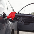 Refueling nozzle in the tank black car at fuel filling column — Stock Photo