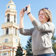 Stock Photo: Young beautiful womphotographing city's attractions