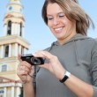 Young beautiful woman holding camera and smiling - Foto Stock