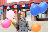 Little girl standing outdoor with color balloons — Stock Photo