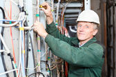 Mature electrician working in hard hat with cables and wires — Stockfoto