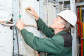 Mature electrician working in hard hat with cables and wires — Stock Photo