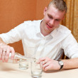 Drunken young man pouring vodka — Stock Photo
