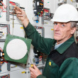 Mature electrician working in white hard hat with caution board — Stock Photo