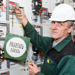 Stock Photo: Mature electrician working in white hard hat with caution board