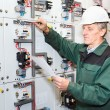 Mature electrician working in hard hat with cables and wires — Stock Photo #7582027