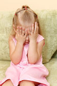 Little child a girl in pink dress sitting on sofa in domestic room — Stock Photo