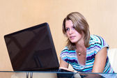 Young woman playing in games on laptop — Stock Photo