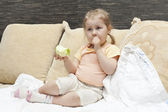 Little child a girl sitting on sofa in domestic room — Stock Photo