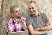 Två män arbetar med dator på park — Stockfoto