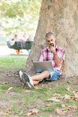 Młody człowiek z komputerem w parku — Zdjęcie stockowe