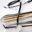 Stock Photo: Stethoscope on stack of paper