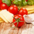 Stock Photo: Pasta, olive oil and tomatoes on the wood background