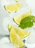 Limes and ice cubes — Stock Photo