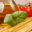 Pasta, olive oil and tomatoes on the wood background — Stock Photo #6972411