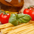 Pasta, olive oil and tomatoes on the wood background — Stock Photo #6975681