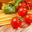 Pasta, olive oil and tomatoes on the wood background — Stock Photo #6975682