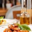 Portion of sesame chicken served on a white plate — Stock Photo