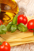 Pasta, olive oil and tomatoes on the wood background — 图库照片