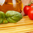 Pasta, olive oil and tomatoes on the wood background — Stock Photo #6984048