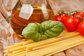 Pasta, olive oil and tomatoes on the wood background — Stock Photo