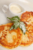 Cheese pancakes with sour cream — Stock Photo