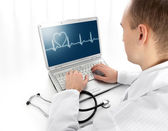 Rear view of a young doctor with laptop — Stock Photo