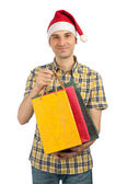 Man in Christmas hat with with gifts — Stock Photo