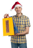 Man with Christmas gifts in a Santa hat — Stok fotoğraf