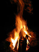 Closeup of burning red fire wood on black background — Stock Photo