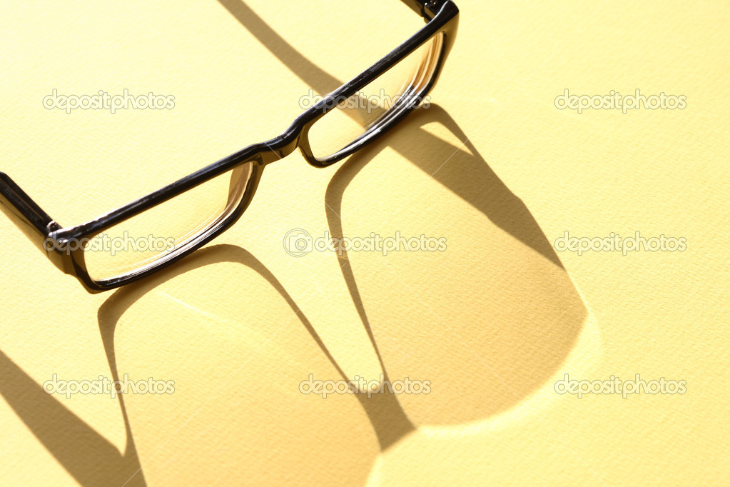Closeup of spectacles with long shadow on yellow surface  Stock Photo #7158599