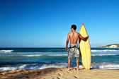 Surfer holding a surf board on beach — Stock Photo