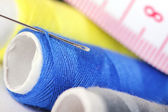 Threads with needle and measure tape — Stock Photo